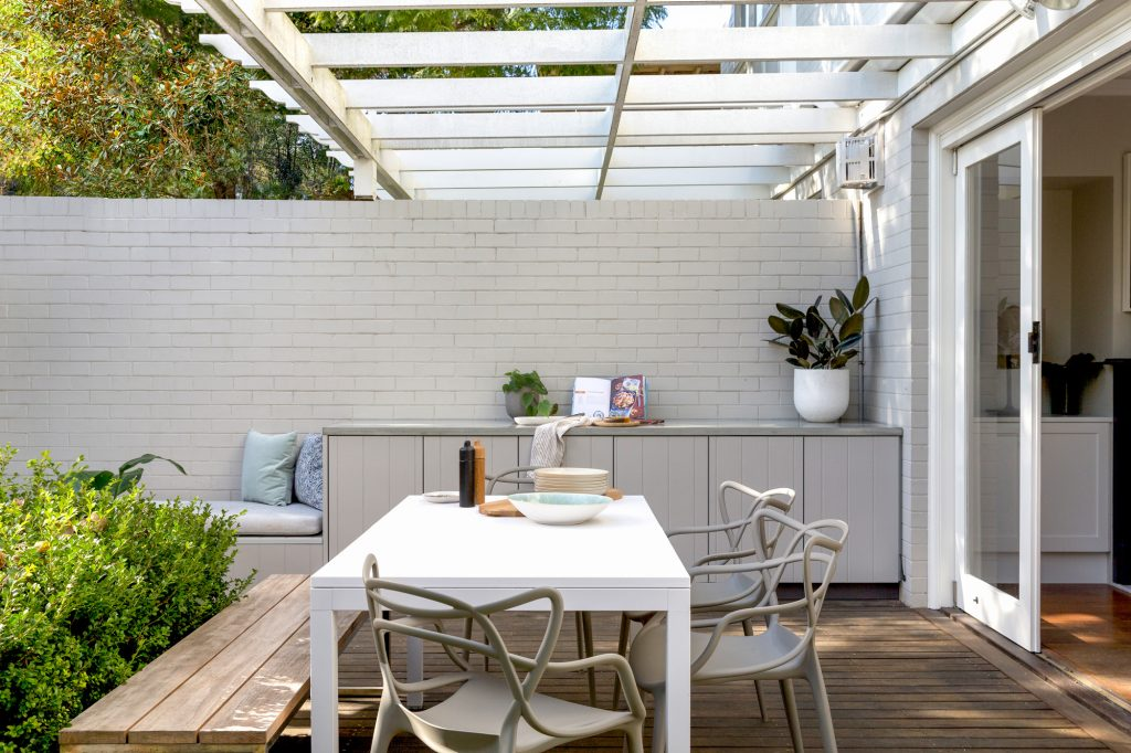 A deck area with built-in storage and a table setting on Sydney's Northern Beaches