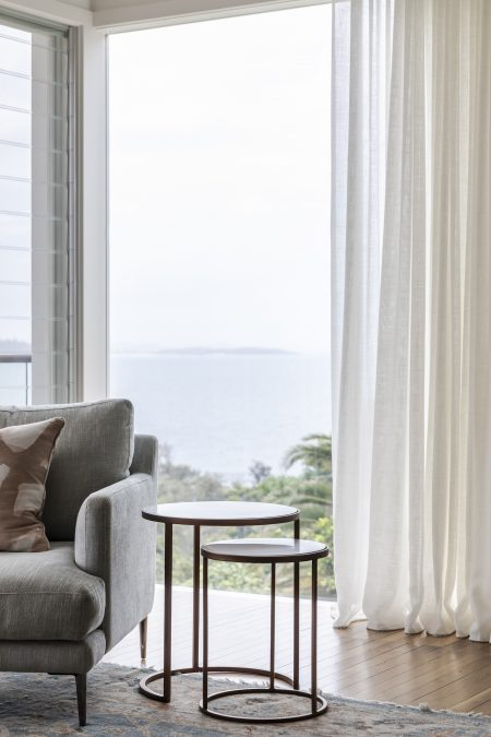 Interior design project in Manly with an armchair and curtains in a living room with a view to the ocean