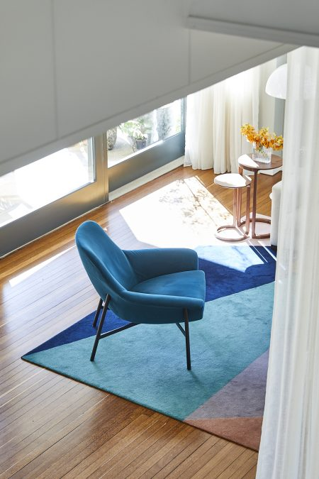 Colourful armchair and rug in a mid century home on Sydney harbour. Interior design and decoration by Alex Gourlay of Vellum Interiors